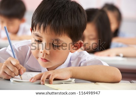 Group Of Students Working At Desks In Chinese School Classroom - stock photo