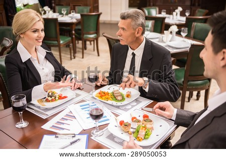 Group of successful business people discussing contract during business lunch. - stock photo
