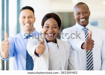 group of successful businesspeople giving thumbs up - stock photo