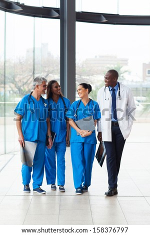 group of successful medical doctors walking in hospital - stock photo