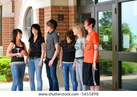 group of teen guys and girls outside of school entrance - stock photo