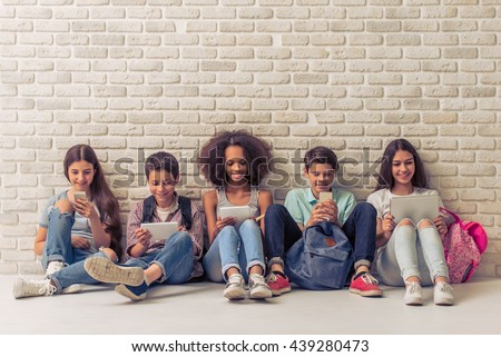 Group of teenage boys and girls is using gadgets and smiling, sitting against white brick wall - stock photo
