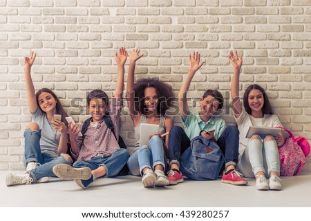 Group of teenage boys and girls is using gadgets, keeping hands up, looking at camera and smiling, sitting against white brick wall - stock photo