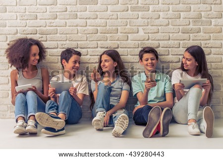 Group of teenage boys and girls is using gadgets, talking and smiling, sitting against white brick wall - stock photo