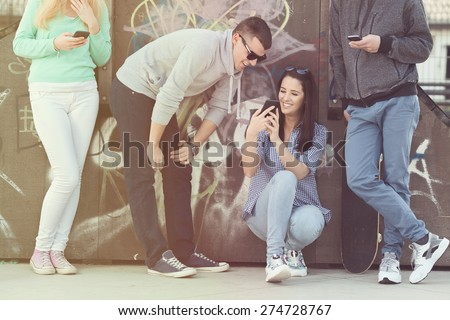 Group of teenage friends using their mobile phones in a skate park or schoolyard. - stock photo