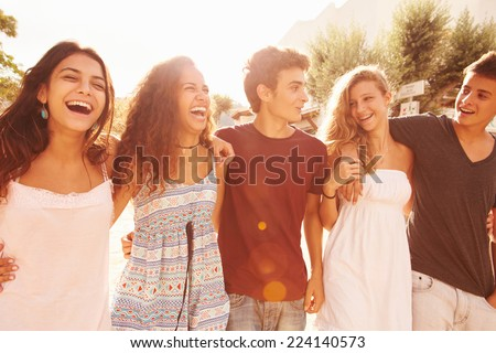 Group Of Teenage Friends Walking Along Street - stock photo