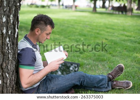 Group of Teenage Students at Park with Computer and Books - stock photo
