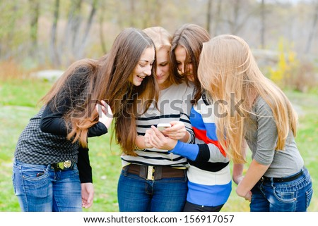 Group Of Teenage Students having fun using mobile phone on the spring or autumn outdoors background - stock photo