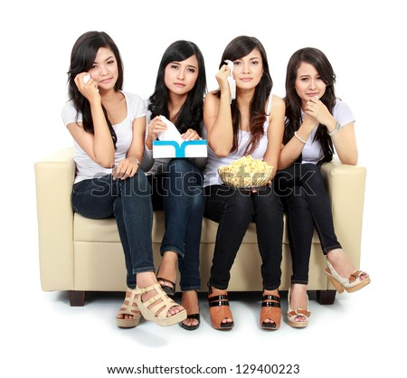 Group of teenager gilrs sitting on couch watching movie with sad expressions - stock photo