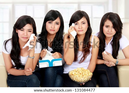 Group of teenager girl sitting on couch watching movie with sad expressions - stock photo