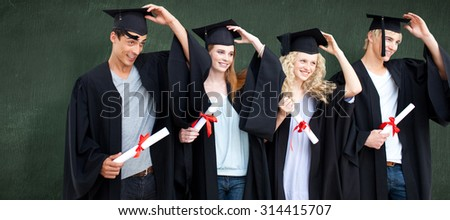 Group of teenagers celebrating after Graduation against green chalkboard - stock photo