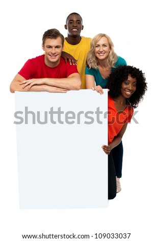 Group of teenagers displaying white banner in front of camera - stock photo