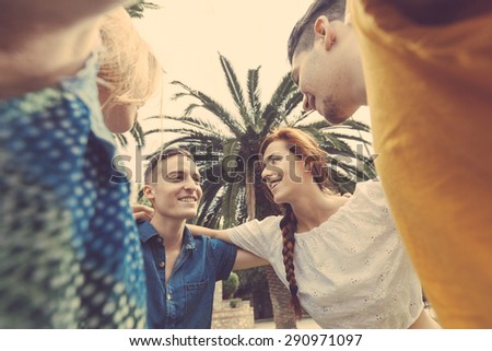 Group of teenagers embraced in circle, bottom view. They are two girls and two boys, smiling and looking down to the camera. - stock photo