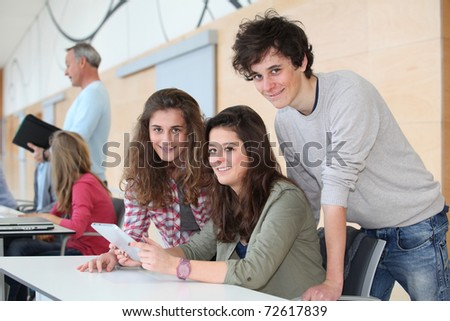Group of teenagers in classroom with electronic tablet - stock photo