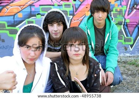 Group of teenagers in front of graffiti - stock photo