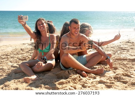 Group of teenagers in the beach with cellphones - stock photo