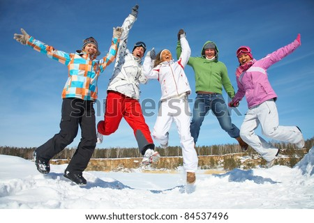 Group of  teenagers jumping together in wintertime - stock photo