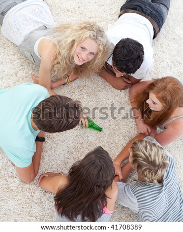Group of teenagers lying on the floor and playing spin the bottle - stock photo