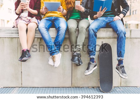 Group of teenagers making different activities sitting in an urban area - stock photo