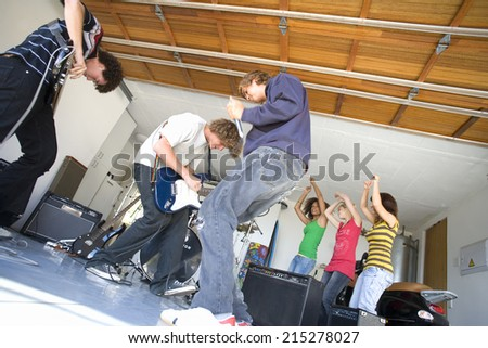 Group of teenagers (16-18) playing in garage band, low angle view - stock photo
