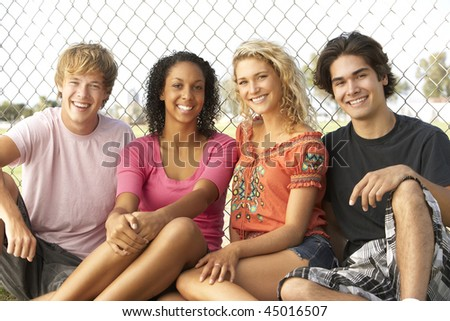 Group Of Teenagers Sitting In Playground - stock photo