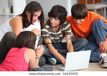 Group of teenagers sitting on the floor in front of a laptop computer - stock photo