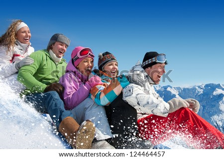 Group of  teenagers slide downhill in winter resort - stock photo