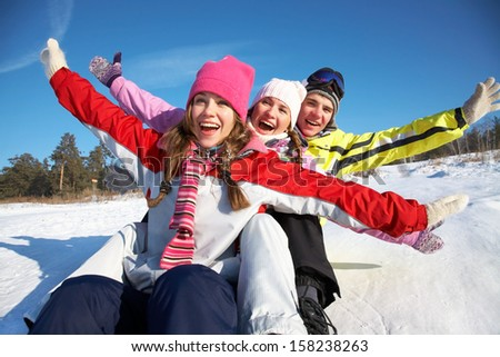 Group of  teenagers slide downhill in wintertime - stock photo