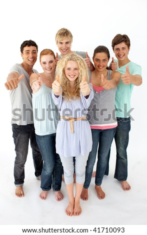 Group of teenagers standing and smiling in front of the camera with thumbs up - stock photo