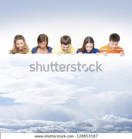 Group of teenagers with a giant, blank, white billboard over the sky background - stock photo