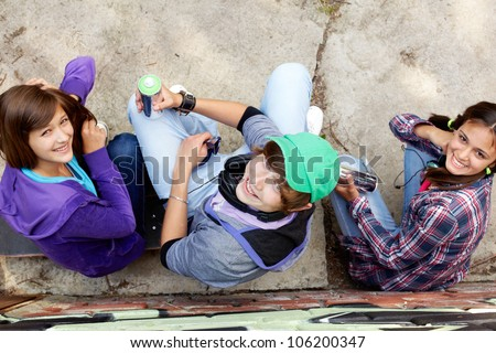 Group of teenagers with aerosol paint sitting and looking up at the camera - stock photo