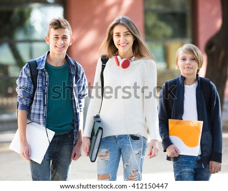 Group of teens going to school with papers for study in summer - stock photo