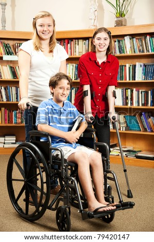Group of teens in the library - one is in a wheelchair, one is on hand crutches. - stock photo
