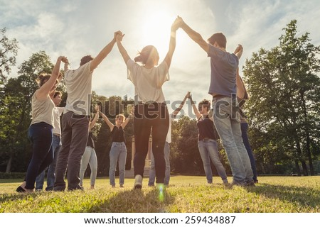 Group of ten friends at the park holding hands - stock photo