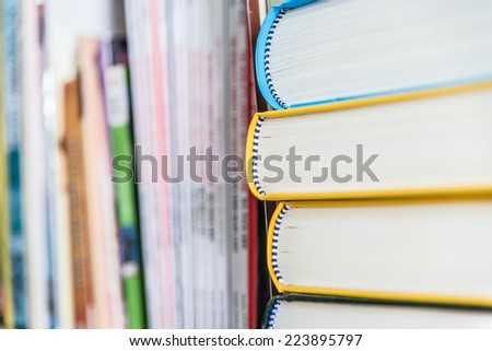 Group of textbooks on book shelf closeup from view side - stock photo