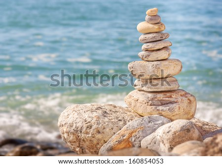 Group of textured Zen stones with blue ocean water background. Neatly ordered pyramid shape natural rock pile balanced on larger rocks. Horizontal nature photo. - stock photo