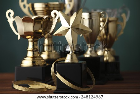 Group of the trophies on the green background - stock photo