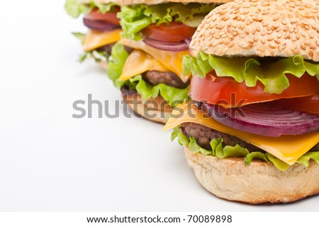 group of three big tasty  cheeseburgers in a row on white background - stock photo