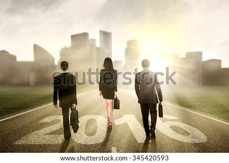 Group of three businesspeople walking together on the road with numbers 2016 toward the city - stock photo