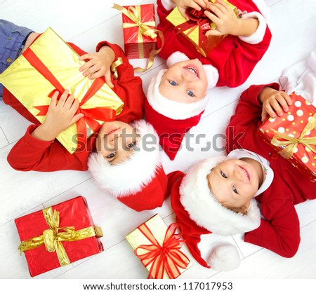 Group of three children in Christmas hat with presents on floor - stock photo