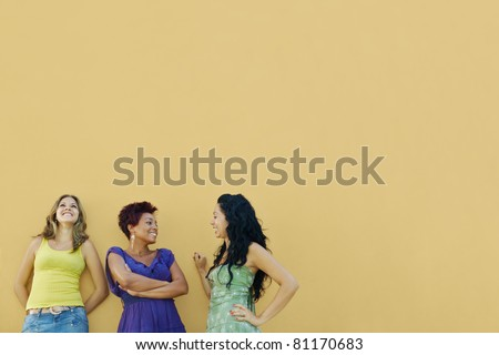 group of three female hispanic friends leaning on yellow wall and laughing. Horizontal shape, waist up, copy space - stock photo