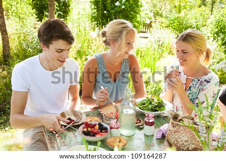 Group of three friends having an outdoors picnic in the summer garden - stock photo