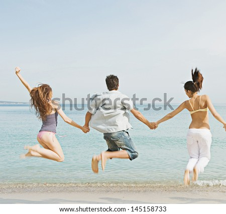 Group of three friends holding hands and jumping at once on the shore of a golden sand beach against a blue sea and sky, expressing energy, fun and joy. - stock photo