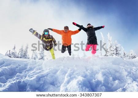 Group of three friends jumps like superhero into snowdrift. Sheregesh resort, Siberia Russia - stock photo