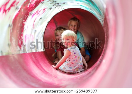 Group of three happy children, cute toddler girl and twin teenage brothers, enjoying summer vacation day sliding together in playground at the park - stock photo