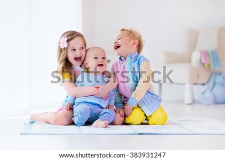 Group of three kids playing in a white bedroom. Children play at home. Preschooler girl, toddler boy and baby in nursery. Happy little brothers and sister bonding having fun together. Siblings love. - stock photo