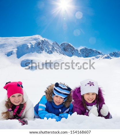 Group of three kids 5-10 years old boys and girls on snow in a row day in mountains - stock photo