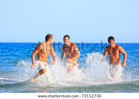 Group of three male friends having lots of fun in their vacation in Greece - stock photo
