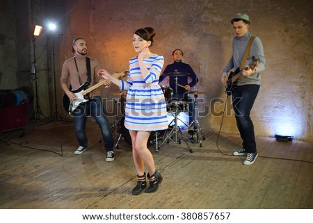 Group of three musicians with musical instruments and a girl singer - stock photo