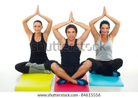 Group of three people doing yoga  on colorful gymnastics mats - stock photo